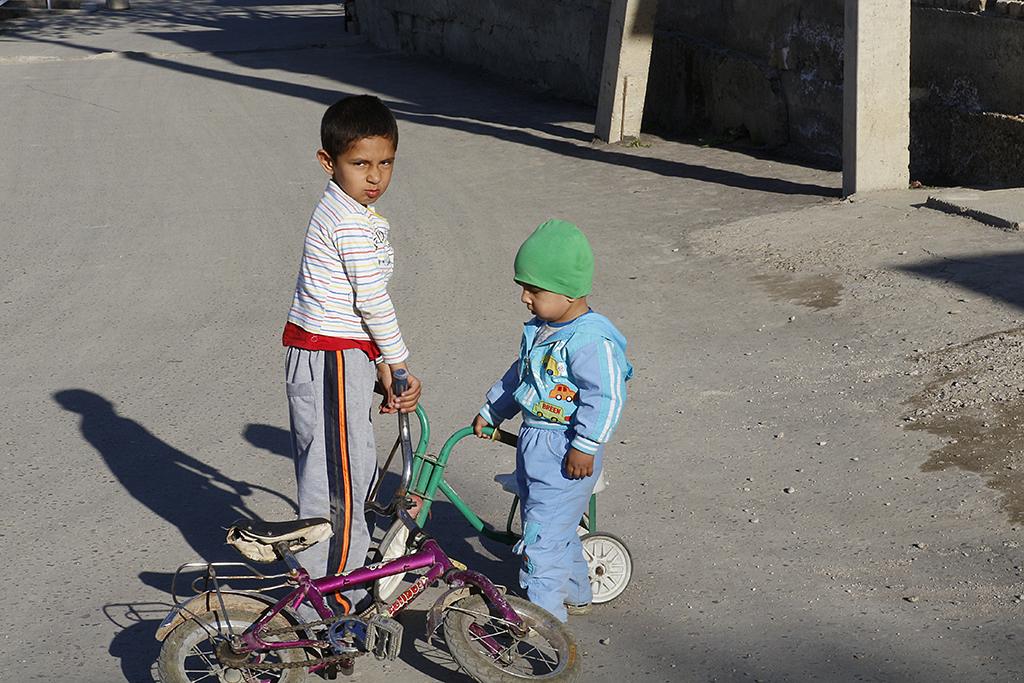 Dos niños jugando con las bicis en Bukhara