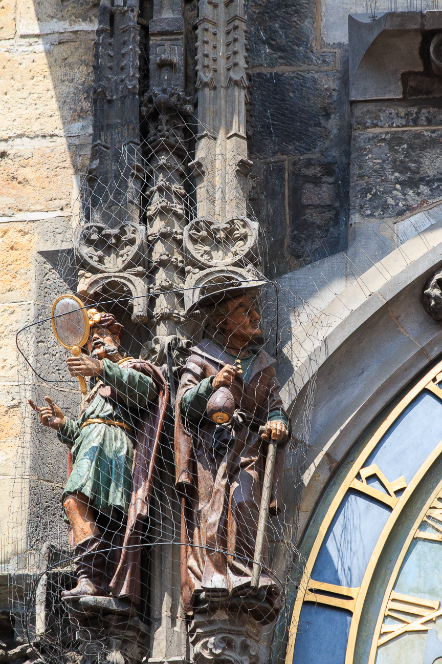 Hombre con espejo y comerciante judio en el reloj de Praga
